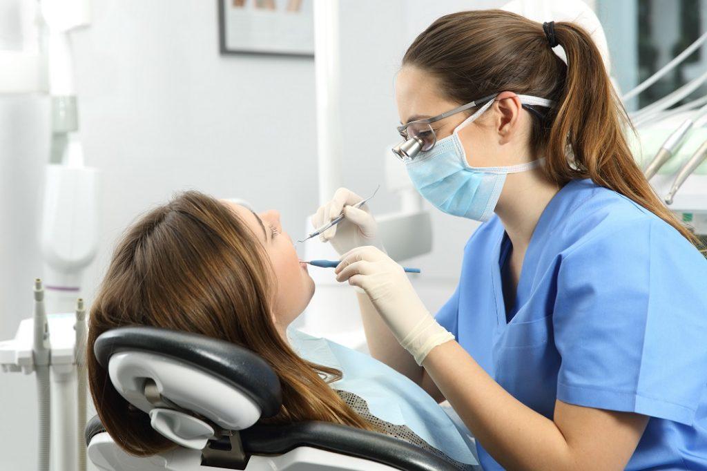 Dentista realizando o procedimento na paciente